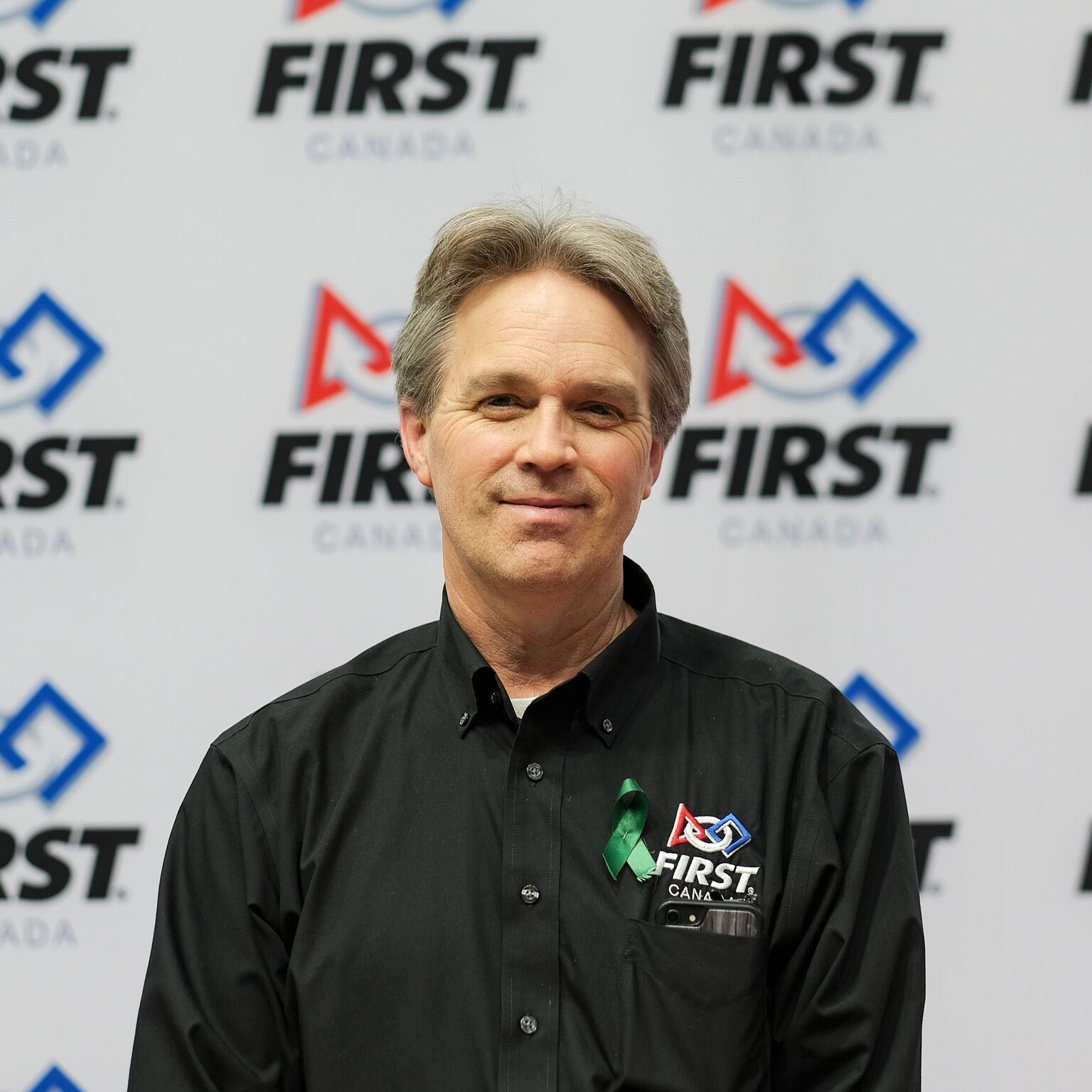 Man in a black shirt with a FIRST Canada Logo